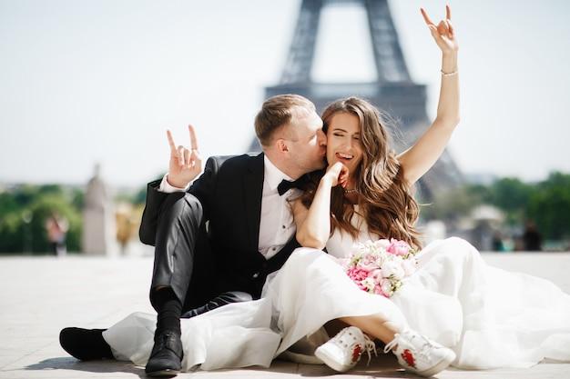 Bride siedzi w snickers przed wieżą eiffla w paryżu, podczas gdy pan młody całuje ją