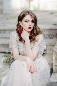 Bride.young modelka z doskonałej skóry i makijażu, białe tło. piękna panna młoda na tło białych schodkach. kobieta w długiej białej sukni siedzi na schodach.