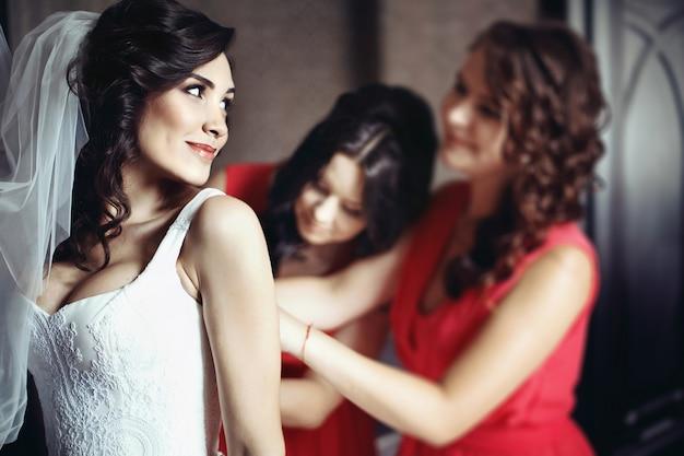Bridesmaids w czerwonych sukienkach pomóż pięknej narzeczonej przygotować się na jej ślub