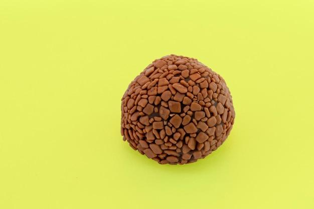 Brigadeiro, ręcznie robione czekoladowe bonbon na białym tle na żółtym tle. brazylijskie słodycze