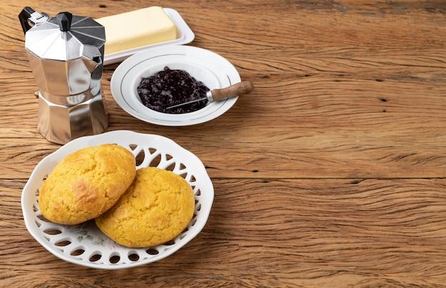 Broa, typowy brazylijski chleb z mąki kukurydzianej z masłem, dżemem, kawą i kopią miejsca.