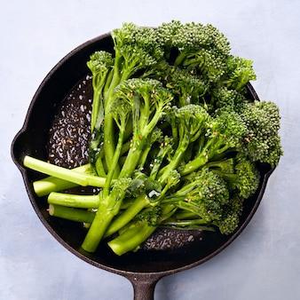 Broccolini świeże organiczne brokuły różyczki zielone warzywa małe brokuły, oliwa z oliwek, nasiona sezamu w obsadzie.