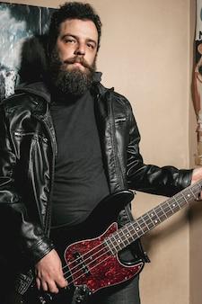 Broda mężczyzna gra na gitarze basowej