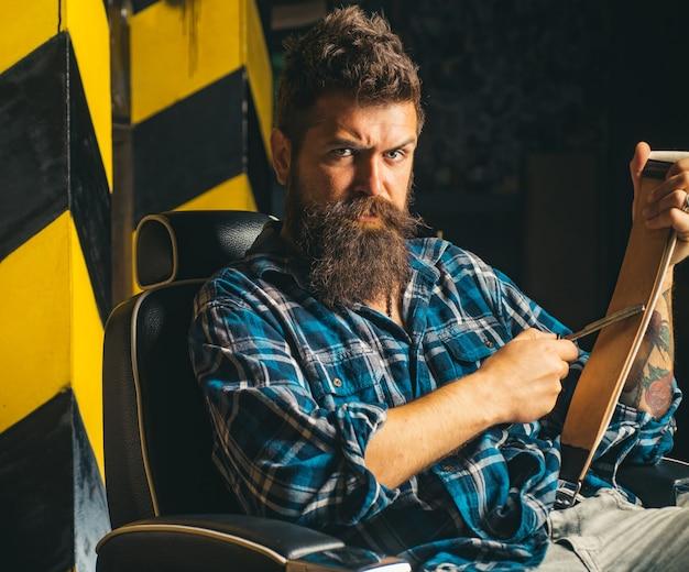 Broda mężczyzna ostrzy brzytwę w salonie fryzjerskim. ostry jak brzytwa. człowiek do golenia i człowiek brzytwy. salony fryzjerskie. brodaty mężczyzna.