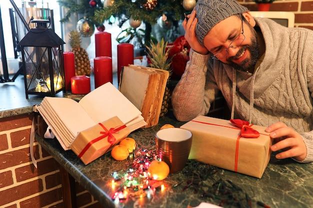 Broda mężczyzna piszący prezenty świąteczne na stole ze starymi książkami