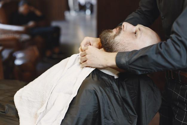 Brodacz. fryzjer z klientem. człowiek z pędzelkiem.