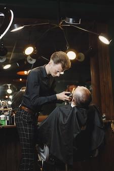 Brodacz. fryzjer z klientem. mężczyzna z goleniem.