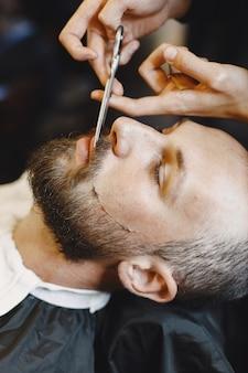 Brodacz. fryzjer z klientem. mężczyzna z grzebieniem i nożyczkami