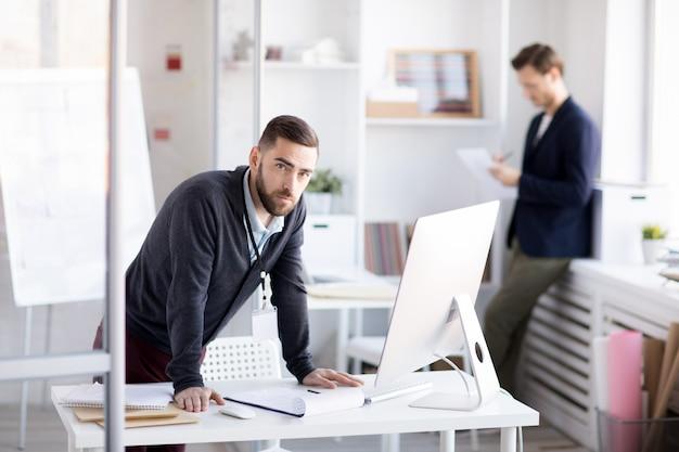 Brodata biznesmen pozycja przy biurkiem
