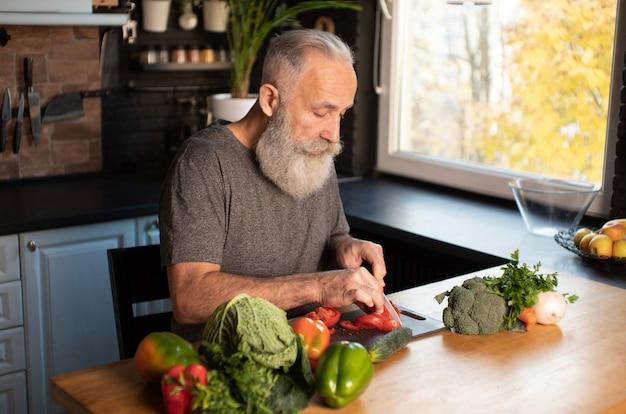 Brodatego starszego mężczyzna tnący warzywa na drewnianej desce