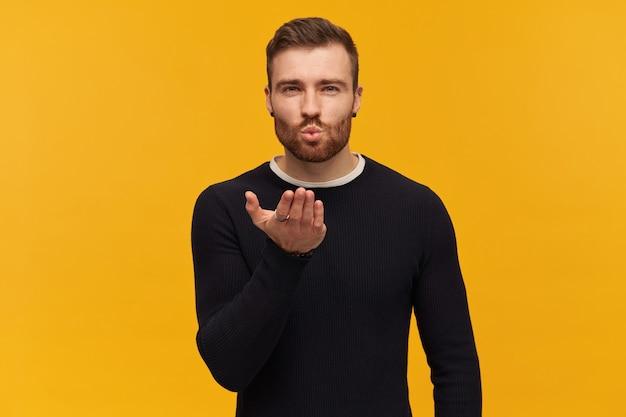 Brodaty atrakcyjny mężczyzna, zalotny facet z brunetką. ma piercing. nosi czarny sweter. wyciąga usta i przesyłając pocałunek. wyciągnięta dłoń. pojedynczo na żółtej ścianie