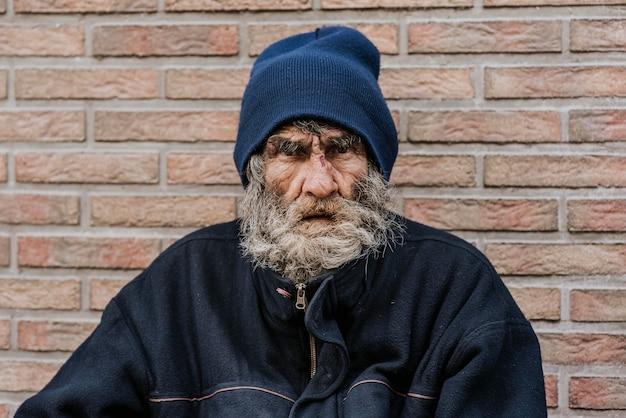 Brodaty bezdomny przed ścianą