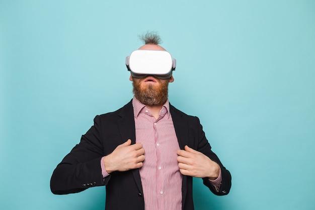 Brodaty biznesmen europejski w ciemnym garniturze na białym tle, podekscytowany zdumiony dotyk powietrza w okularach wirtualnej rzeczywistości
