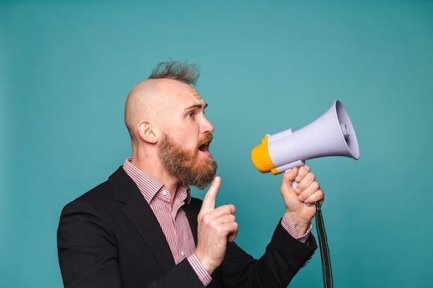 Brodaty biznesmen europejski w ciemnym garniturze na białym tle, z megafonem krzyczy z poważną gniewną twarzą, prosząc o uwagę