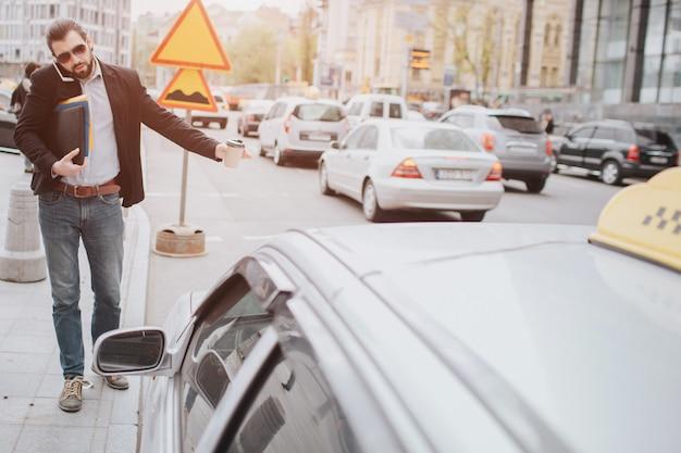 Brodaty biznesmen łapie taxi z filiżanką. nie ma czasu, będzie rozmawiać przez telefon w drodze. człowiek robi wiele zadań. wielozadaniowość mężczyzna biznesowy.