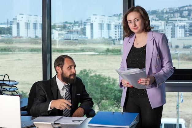 Brodaty biznesmen na sobie krawat i czarny garnitur i jego asystent sekretarza w swoim biurze. sekretarz przyniósł szefowi dokumenty do podpisu, szef podpisuje dokumenty. flirt w miejscu pracy