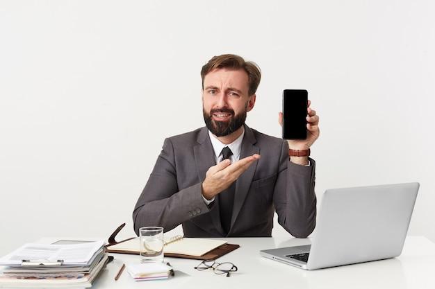 Brodaty biznesmen, najwyższy menadżer siedzi przy biurku w biurze, patrzy na aparat i chce zwrócić twoją uwagę na swojego smartfona, ubrany w drogi garnitur z krawatem. pojedynczo na białej ścianie.