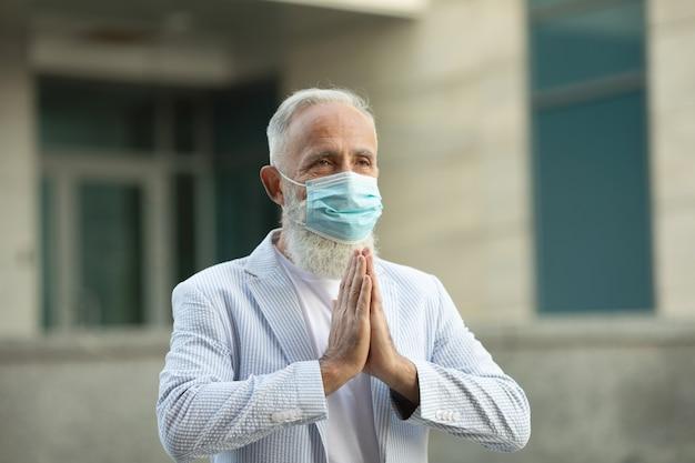 Brodaty biznesmen noszący maskę i pozdrowienia z namaste, aby zapobiec rozprzestrzenianiu się wirusa