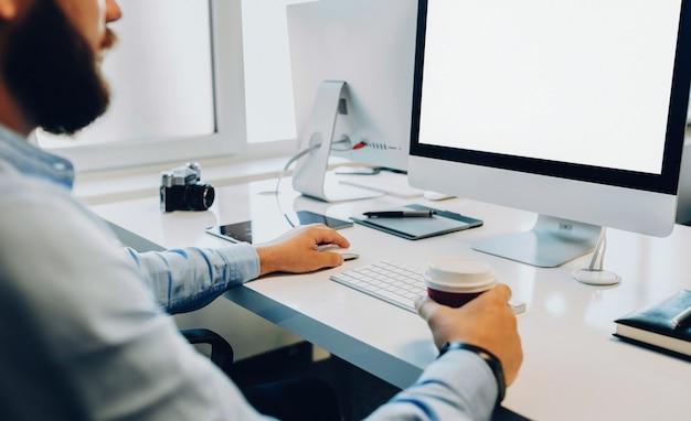 Brodaty biznesmen siedział przy komputerze podczas picia kawy
