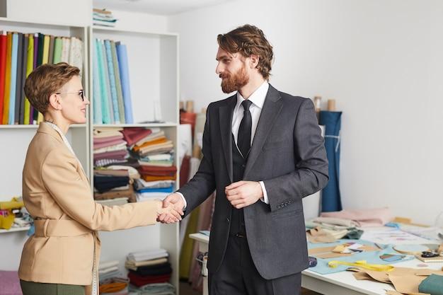 Brodaty biznesmen w garniturze, ściskając rękę z projektantem, witają się w warsztacie