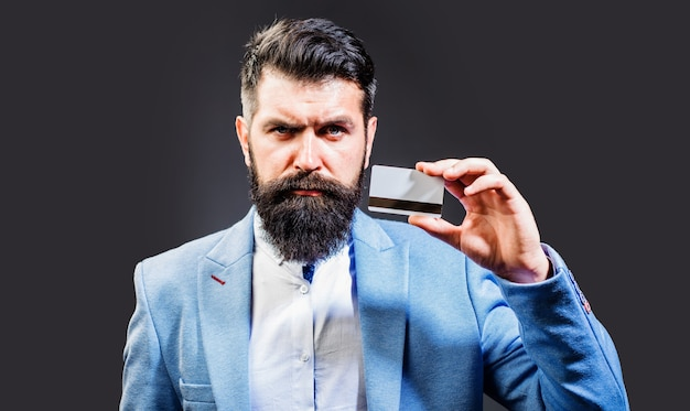 Brodaty biznesmen w garniturze z kartą kredytową. pieniądze i finanse. handel, wymiana, dług. zapłata. koncepcja bankowości.