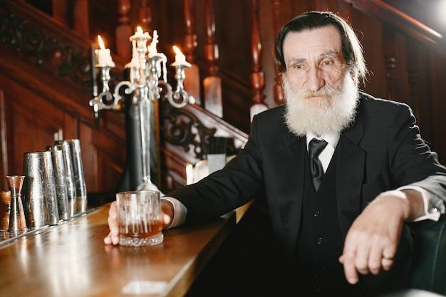 Brodaty biznesmen w podeszłym wieku. mężczyzna pije whisky. starszy w czarnym garniturze.