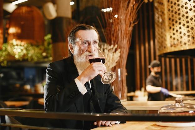 Brodaty biznesmen w podeszłym wieku. mężczyzna w restauracji. starszy w czarnym garniturze.