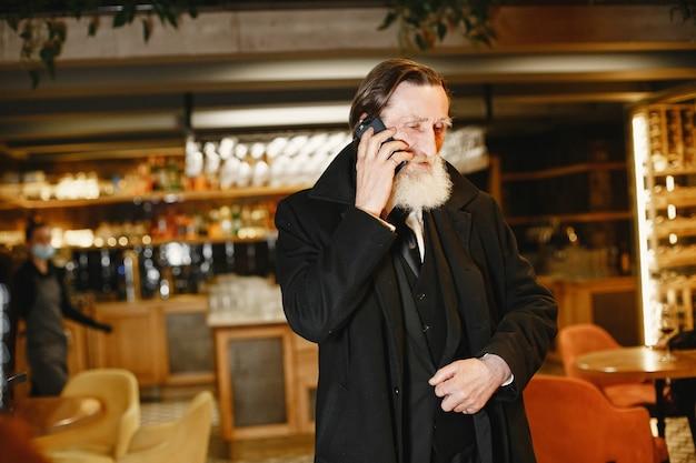 Brodaty biznesmen w podeszłym wieku. mężczyzna z telefonem komórkowym. starszy w czarnym garniturze.