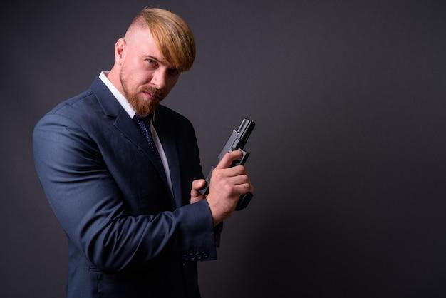 Brodaty biznesmen z pistoletem na szaro