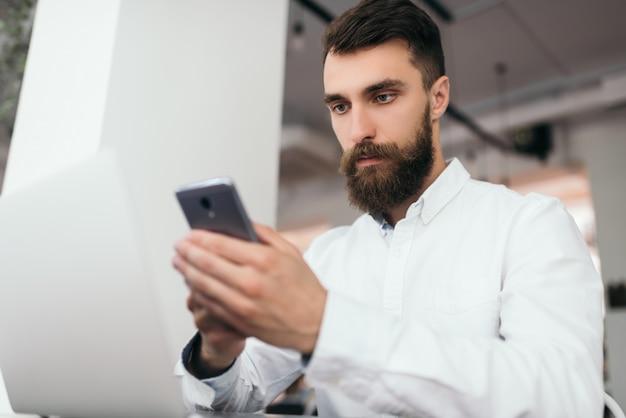 Brodaty biznesmen za pomocą laptopa i smartfona