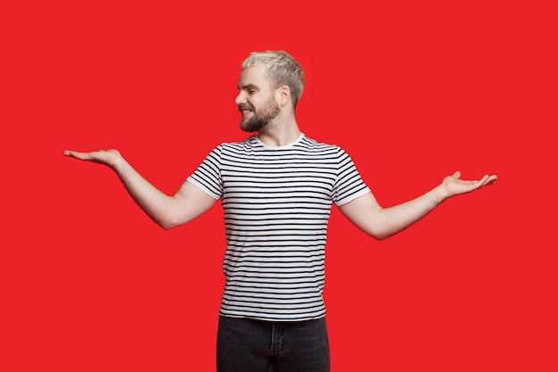 Brodaty blondyn porównuje rzeczy na swoich dłoniach, pozując i uśmiechając się na czerwonej ścianie
