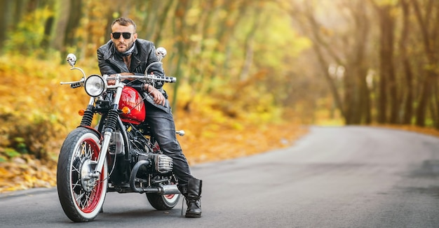 Brodaty brutalny mężczyzna w okularach przeciwsłonecznych i skórzanej kurtce siedzi na motocyklu na drodze w lesie