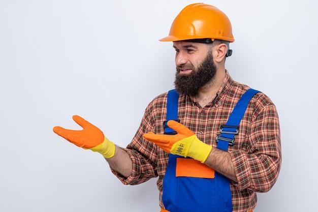 Brodaty budowniczy mężczyzna w mundurze budowlanym i hełmie ochronnym w gumowych rękawiczkach, patrząc na bok, prezentując ramionami rąk
