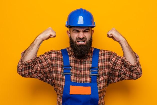Brodaty budowniczy mężczyzna w mundurze budowlanym i kasku ochronnym krzyczy z agresywną miną, podnosząc pięści i jest sfrustrowany