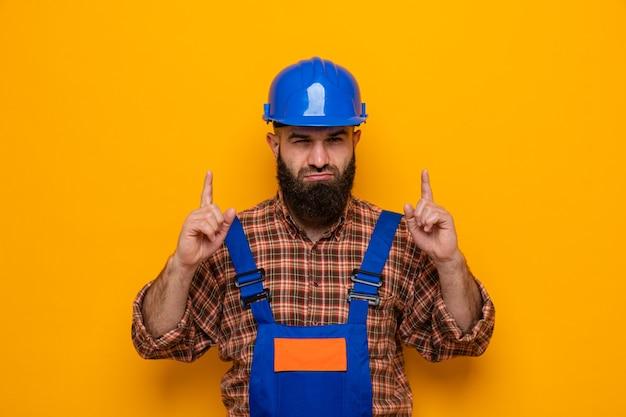 Brodaty budowniczy mężczyzna w mundurze budowlanym i kasku ochronnym, patrząc z poważną twarzą, wskazując palcami wskazującymi w górę