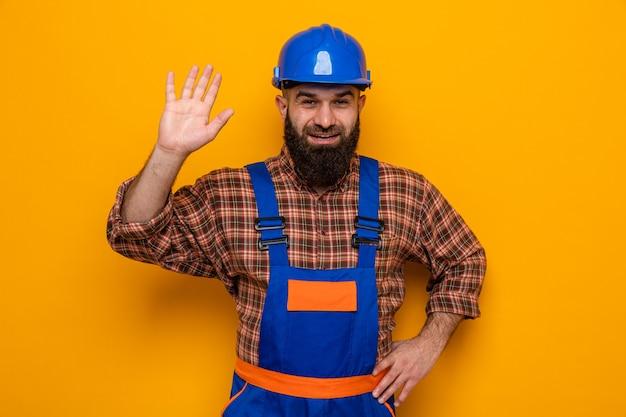 Brodaty budowniczy mężczyzna w mundurze budowlanym i kasku ochronnym, patrzący uśmiechnięty radośnie, machający ręką