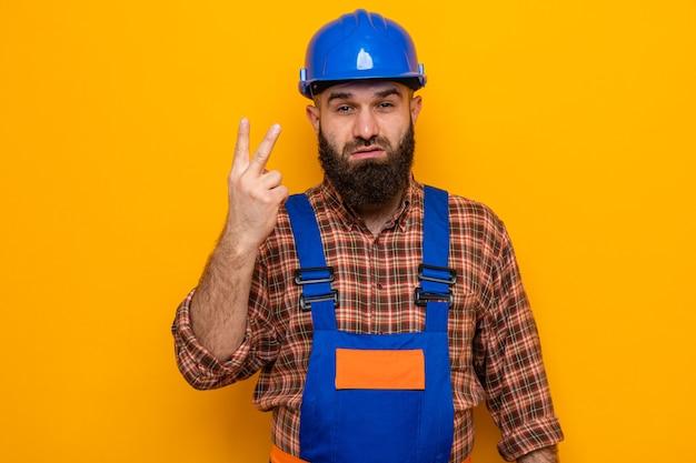 Brodaty budowniczy mężczyzna w mundurze budowlanym i kasku ochronnym, patrzący z poważną twarzą pokazującą numer dwa palcami