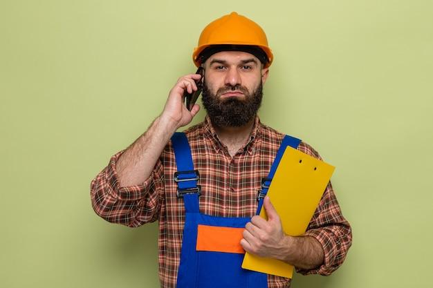 Brodaty budowniczy mężczyzna w mundurze budowlanym i kasku ochronnym, trzymając schowek, patrząc z poważną twarzą, rozmawiając na telefonie komórkowym