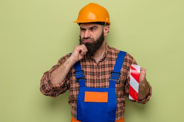 Brodaty budowniczy mężczyzna w mundurze budowlanym i kasku ochronnym, trzymający taśmę samoprzylepną, patrząc na bok z zamyślonym wyrazem twarzy na myśleniu