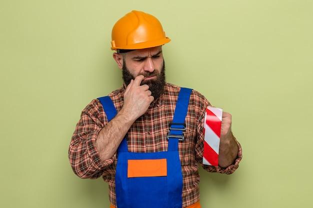 Brodaty budowniczy mężczyzna w mundurze budowlanym i kasku ochronnym, trzymający taśmę samoprzylepną, patrząc na to zaintrygowany, stojąc na zielonym tle