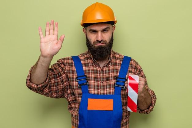 Brodaty budowniczy mężczyzna w mundurze budowlanym i kasku ochronnym, trzymający taśmę samoprzylepną, patrząc z poważną twarzą, wykonując gest zatrzymania ręką