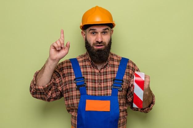 Brodaty budowniczy mężczyzna w mundurze budowlanym i kasku ochronnym, trzymający taśmę samoprzylepną, patrzący z uśmiechem na twarzy pokazujący palec wskazujący mający nowy pomysł