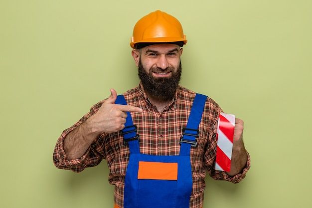 Brodaty budowniczy mężczyzna w mundurze budowlanym i kasku ochronnym, trzymający taśmę samoprzylepną wskazującą na nią palcem wskazującym, uśmiechający się radośnie