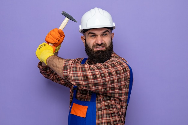 Brodaty budowniczy mężczyzna w mundurze budowlanym i kasku ochronnym w gumowych rękawiczkach, kołysząc młotkiem, patrząc z gniewną twarzą