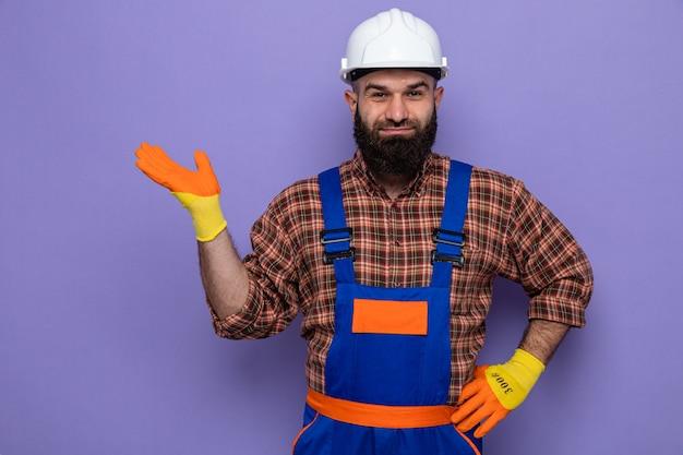 Brodaty budowniczy mężczyzna w mundurze budowlanym i kasku ochronnym w gumowych rękawiczkach, patrzący uśmiechnięty radośnie, prezentujący się z ramieniem dłoni
