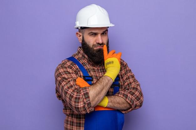 Brodaty budowniczy mężczyzna w mundurze budowlanym i kasku ochronnym w gumowych rękawiczkach, patrzący z poważnym myśleniem o twarzy