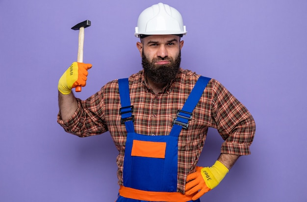 Brodaty budowniczy mężczyzna w mundurze budowlanym i kasku ochronnym w gumowych rękawiczkach, trzymając młotek, patrząc na kamerę z poważną twarzą stojącą na fioletowym tle