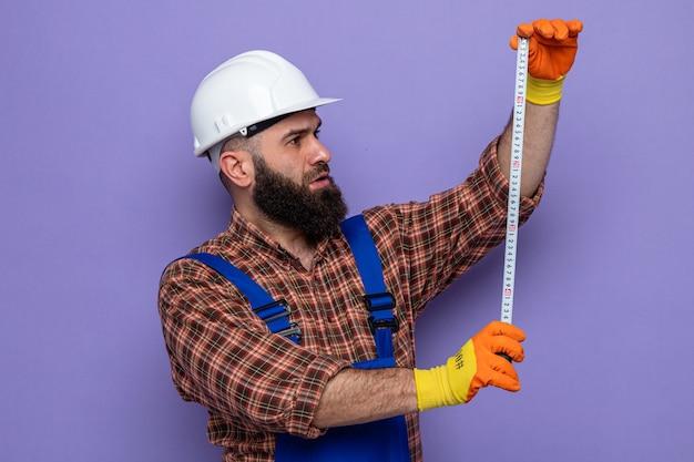 Brodaty budowniczy mężczyzna w mundurze budowlanym i kasku ochronnym w gumowych rękawiczkach, trzymający taśmę mierniczą, patrząc na to z poważną twarzą stojącą na fioletowym tle