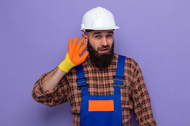Brodaty budowniczy mężczyzna w mundurze budowlanym i kasku ochronnym w gumowych rękawiczkach wyglądający na zaintrygowanego, trzymający rękę nad uchem, próbujący słuchać plotek stojących na fioletowym tle