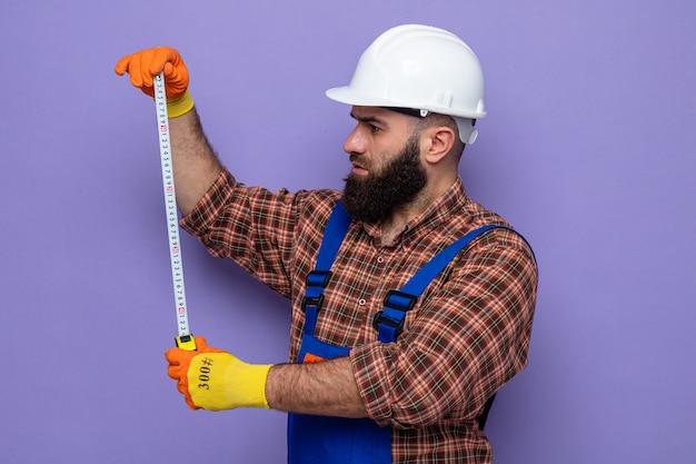 Brodaty budowniczy mężczyzna w mundurze budowlanym i kasku ochronnym w gumowych rękawiczkach, wyglądający pewnie pracując za pomocą taśmy mierniczej stojącej na fioletowym tle